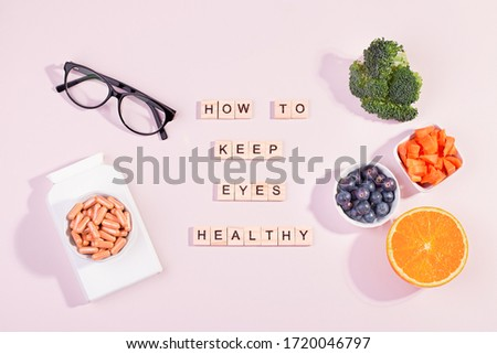 Essential vitamins and supplements to keep eyes healthy on pink background. Eyeglasses, vitamin pills, food containing vitamins for good eyesight with text healthy eyes, top view, pink table top Royalty-Free Stock Photo #1720046797