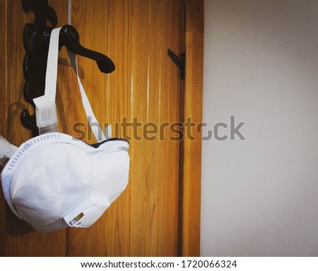 Protective face mask hanging on door handle