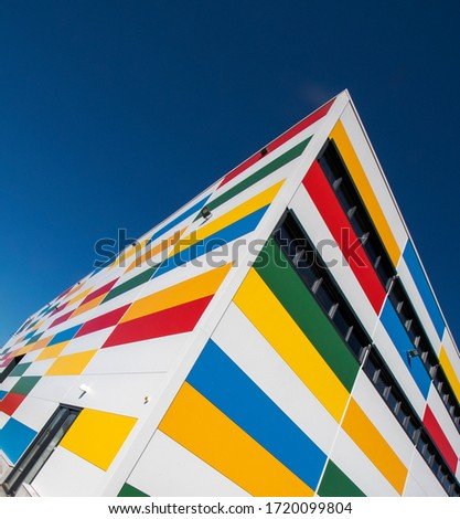 Multi-colored facades of a modern building with black window frames.  #1720099804