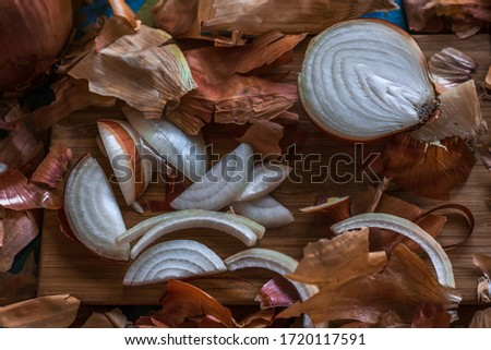 onion husks lie on the table, a lot of brown onion husks, onion husks and sliced onions lie on a striped tablecloth in dark lighting, a very beautiful still life with onions and onion husks #1720117591