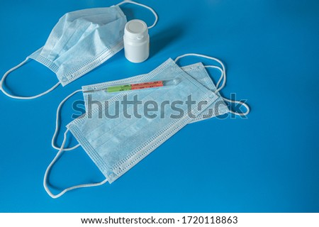 Prevention of the coronavirus pandemic, medical face mask, thermometer, pill bottle, on a blue background. #1720118863