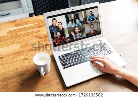 Video call. A group of people on laptop screen, app for video online communication. Female hands on the keyboard, cup of coffee near #1720135582