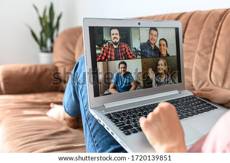 Meeting with friends using online video call at laptop while staying home on self-isolation, quarantine. Closeup screen with a several people profiles #1720139851