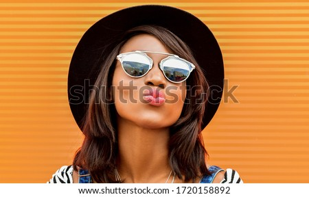 Beautiful smiling african woman in a black hat over colorful red background. Fashion portrait stylish woman in sunglasses outdoor. Royalty-Free Stock Photo #1720158892