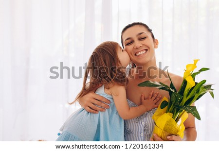 Caucasian little girl in blue dress is kissing her mom and giving her yellow flowers #1720161334