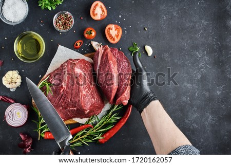 The butcher shows a section of fresh meat tenderloin, which lies on parchment on a dark background. On the table-seasonings, spices, vegetables and herbs. Top view, free space for text. #1720162057