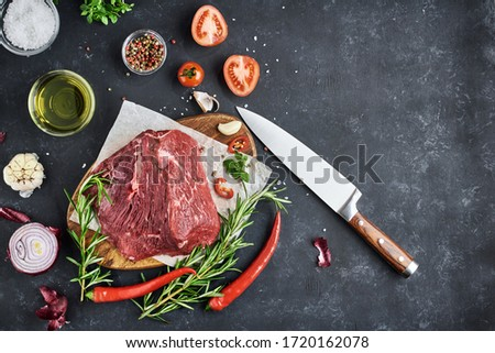 A large piece of fresh meat tenderloin lies on parchment on a dark background. Seasonings, spices, vegetables and herbs are on the table. Top view, free space for text. #1720162078
