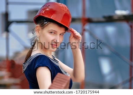 Close-up. A female student of architecture college in practice. There is a safety helmet on her head. #1720175944
