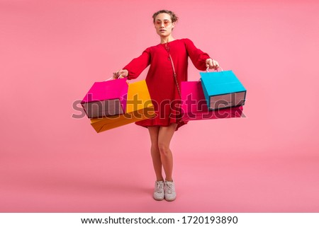 attractive happy smiling stylish woman shopaholic in red trendy dress holding colorful shopping bags on pink studio background isolated, sale excited, fashion trend #1720193890