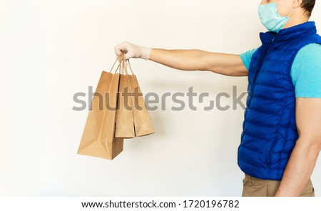 Delivery man in uniform face mask gloves reaching out hand with paper packages or bags n front of white background. takeout meal, delivery to home, food delivery, shopping order online. #1720196782