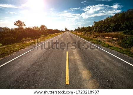 Empty asphalt road through the green field and clouds on blue sky in summer day.  Royalty-Free Stock Photo #1720218937