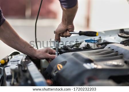 Man master repairs under the hood of the car. Repairing concept