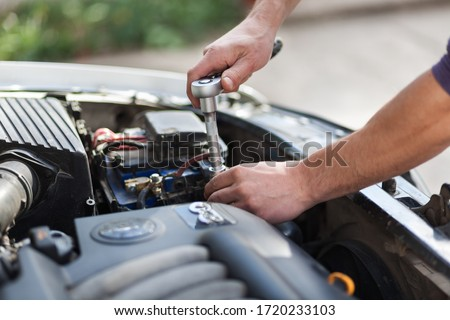 Man master repairs under the hood of the car. Repairing concept