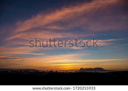 Dawn with the silhouettes of the port cranes and the Rock of Gibraltar in the background. Royalty-Free Stock Photo #1720255933