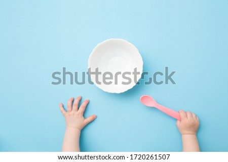 Baby hands holding pink plastic spoon and waiting food. Empty white bowl on light blue table background. Pastel color. Closeup. Point of view shot. #1720261507