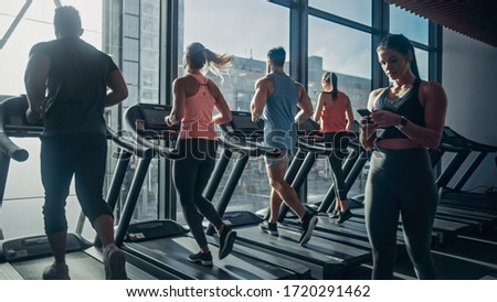 Beautiful Athletic Woman Uses Smartphone Walks Through Fitness Club Gym. Using Social Media, Posting Pictures, Communicating, Checking Email. In the Background Sports People Running on Treadmills