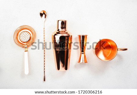 Copper bar tools and accessories for making cocktail. Shaker, jigger, strainer, spoon, tongs, muddler. Alcohol drink and beverages preparation concept. White background, top view, copy space #1720306216
