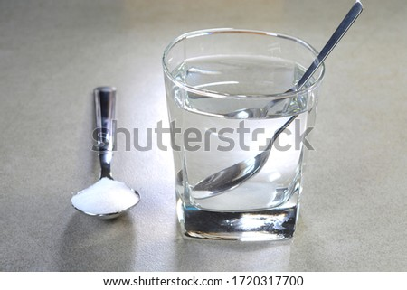 Salt water in a glass cup and salt in a teaspoon. Salt water has high level of minerals and salt water gargle helps in removing of cold and sore throat. #1720317700