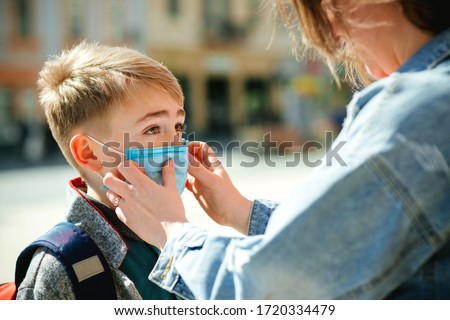 Mother puts a safety mask on her son's face. Schoolboy is ready go to school. Cute boy with a backpack outdoors. Back to school concept. Medical mask to prevent coronavirus. Coronavirus quarantine #1720334479