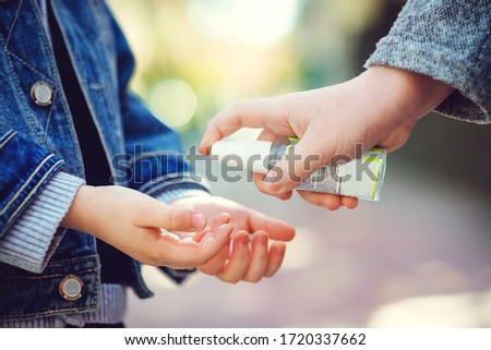 Kids hands using sanitizer gel, closeup. Children disinfecting hands with antiseptic gel. Coronavirus epidemic. Coronavirus quarantine. Sanitizer for prevent spread of germs, bacteria, coronavirus Royalty-Free Stock Photo #1720337662