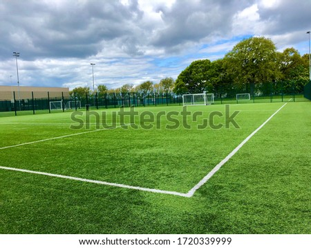 Football pitch and a cloudy sky. Green field. England. Royalty-Free Stock Photo #1720339999