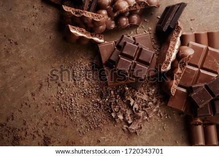 Composition of bars and pieces of different milk and dark chocolate, grated cocoa on a brown background top view close up #1720343701