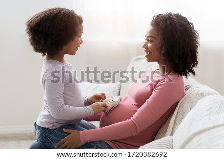 Little Black Girl Placing Baby Shoes At Pregnant Mom's Belly While They Sitting Together On Couch In Living Room, Playing And Bonding, Side View #1720382692