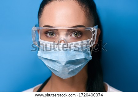large portrait of a young girl, brunette with gathered hair in safety glasses with green eyes, a protective medical mask looks straight, dressed in a white long sleeves on a blue background soft focus Royalty-Free Stock Photo #1720400074