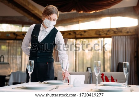A waiter in a medical protective mask serves the table in the restaurant #1720419277