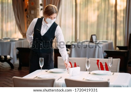 A waiter in a medical protective mask serves the table in the restaurant #1720419331