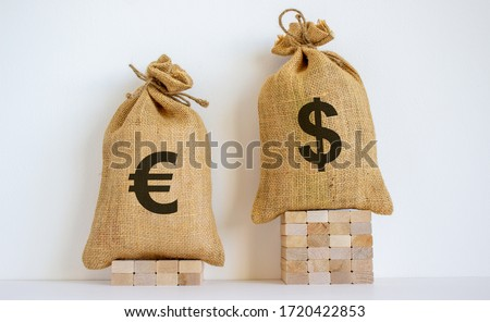 2 canvas bags with simbols of dollar and euro standing at different heights. Conceptual picture symbolizing cross currency exchange rates. #1720422853