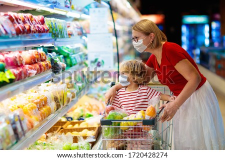 Shopping with kids during virus outbreak. Mother and child wearing surgical face mask buying fruit in supermarket. Mom and little boy buy fresh vegetable in grocery store. Family in shop.  #1720428274