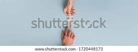 Wide view image of business partners, businessman and businesswoman, joining two blank matching puzzle pieces. Top view over blue background. Royalty-Free Stock Photo #1720448173