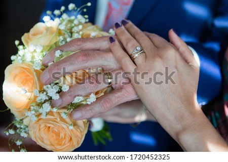 Close up picture of the bride's and elderly groom's hands with yellow gold vintage diamond rings holding together, navy groom's suit, pink tie, wedding bouquet with peach roses