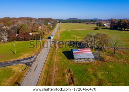 A country road with an American Flag painted on a barn near a farm in the United States #1720466470