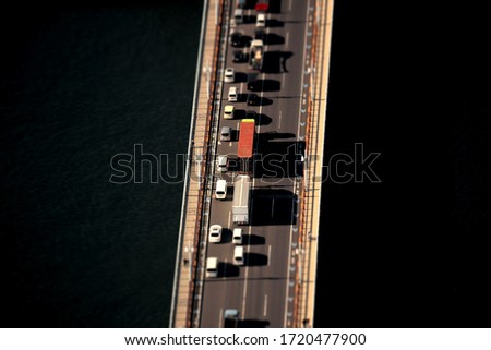A diorama style photo of the traffic situation of cars crossing the bridge seen from above #1720477900