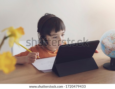 Kid self isolation using tablet for his homework,Child doing using digital tablet searching information on internet during covid 19 lock down,Home schooling,Social Distance,E-learning online education #1720479433
