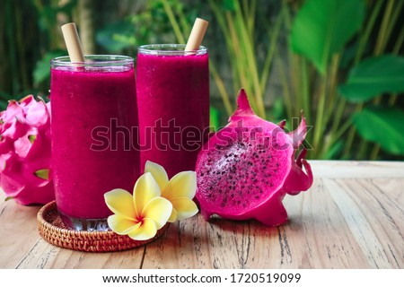 Dragon fruit smoothie in glass on table in tropical cafe outdoor