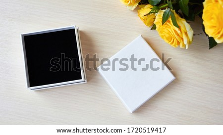 Top view for presentation. Empty box for jewelry, gift. Place for logo, sale text. Yellow roses bouquet on the table.