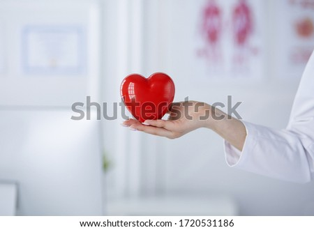 Female doctor with stethoscope holding heart, on light background #1720531186