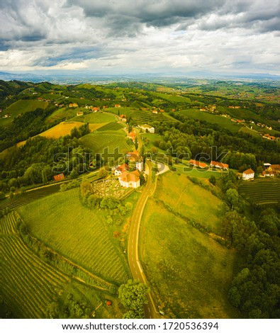 Aerial view of green hills and vineyards with mountains in background. Austria vineyards landscape. Leibnitz area in south Styria, wine country. Tuscany like place and famous tourist spot #1720536394