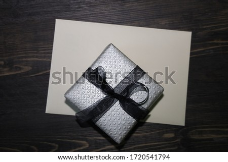 A gift wrapped with silver paper and black bow on top of al greeting card and wooden background.