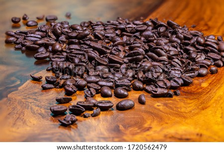 Top view close up to a heap fresh roasted coffee beans on a wooden background. High resolution detailed macro picture on brown roasted coffee beans on tropical wood table. Background  wallpaper image