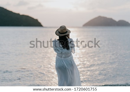 Beautiful asian young pregnant woman with white dress is standing to take a picture of the sunset by the sea at Phangan island in evening time. Blur sea background.split color.