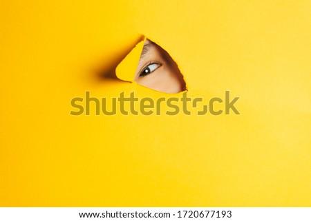 The boy peeks through a cut hole in the yellow paper wall. Human eye closeup. Royalty-Free Stock Photo #1720677193