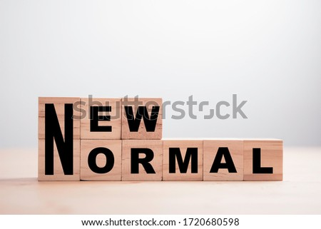 Wooden block cubes for new normal wording. The world is changing to balance it into new normal include business , economy , environment and health. Royalty-Free Stock Photo #1720680598