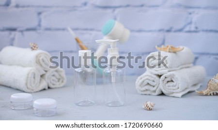 Plastic containers. Spa composition, recreation and hospitality. Beauty and skin care concept.  Plastic bottles, lens containers and white towels on a light background #1720690660