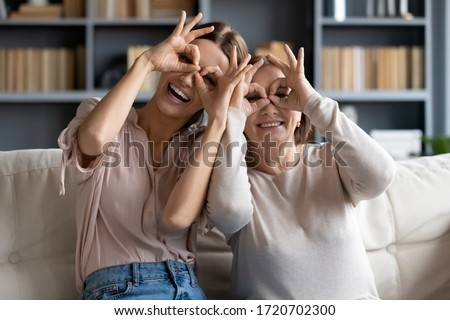 Funny family portrait of adult grown up daughter and mature mother making binoculars gesture, looking at camera, laughing young woman with older mum posing for photo, sitting on couch at home