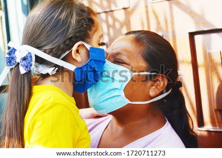 Tender portrait of native american mom with her little daughter. Both wearing masks. Royalty-Free Stock Photo #1720711273
