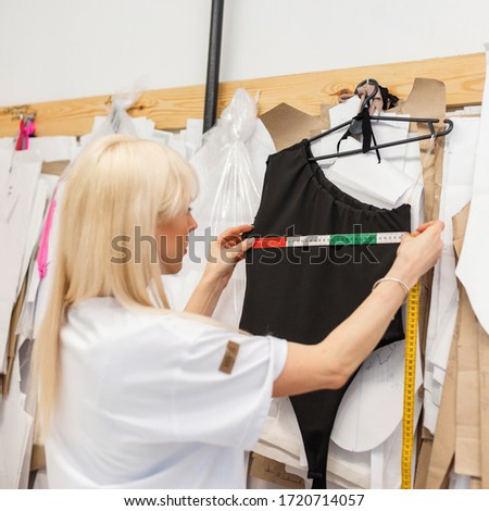 Fashion designer measures clothes in the studio. Tailor works in atelier
